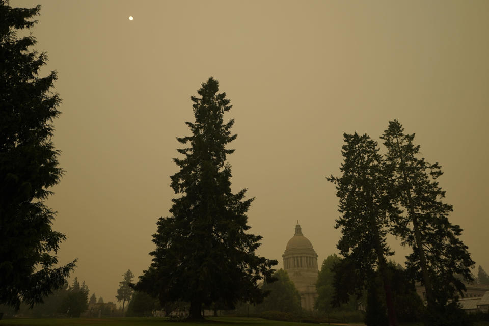 FILE - In this Sept. 12, 2020, file photo, smoke from wildfires in Oregon and California create hazy skies as the sun is seen above the Washington state Capitol in Olympia, Wash. Wildfires churning out dense plumes of smoke as they scorch huge swaths of the U.S. West Coast have exposed millions of people to hazardous pollution levels, causing emergency room visits to spike and potentially thousands of deaths among the elderly and infirm, according to an Associated Press analysis of pollution data and interviews with physicians, health authorities and researchers. (AP Photo/Ted S. Warren, File)