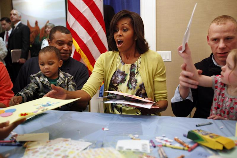 First lady Michelle Obama reacts on receiving multiple Easter cards from families at Fisher House, including Eun White, 3, sitting on his father Army Major Eunotchol White, left, and Madison Tharp, 3, seated with her father Army Staff Sgt. Randy Tharp, right, at Walter Reed National Military Medical Center in Bethesda, Md., Wednesday, April 4, 2012. The Fisher House program houses military families while a family member is receiving medical care. (AP Photo/Jacquelyn Martin)