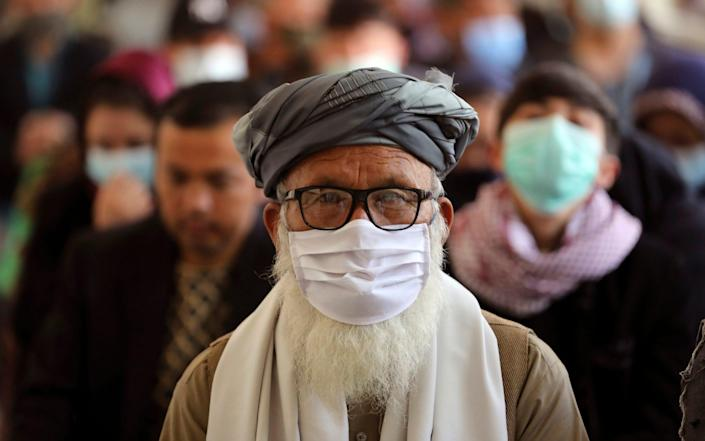 Afghan people wait to receive the Indian version of the AstraZeneca coronavirus vaccine at a hospital in Kabul - AP