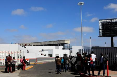 People wait to apply for asylum in the United States outside the El Chaparral border in Tijuana