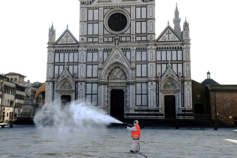 A municipal worker disinfects the Piazza Santa Croce in Florence as part of the measures taken by the Italian government to fight the spread of the COVID-19