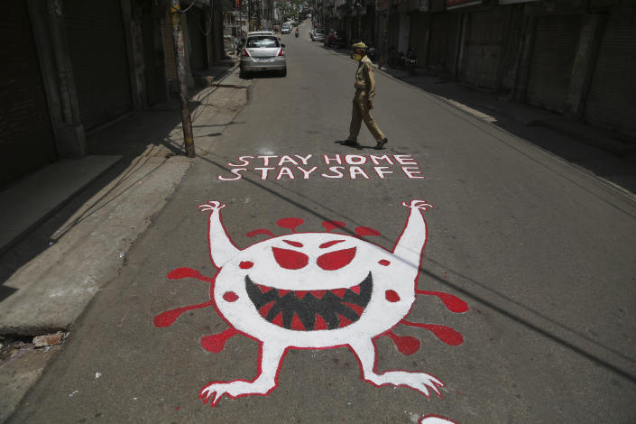 An Indian police man walks past an awareness message painted on a road during a curfew to curb the spread of coronavirus in Jammu, India, Wednesday, May 19, 2021. India has the second-highest coronavirus caseload after the U.S. with more than 25 million confirmed infections.(AP Photo/Channi Anand)