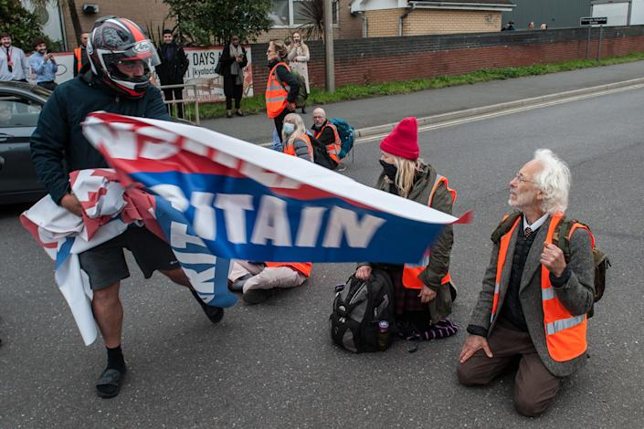 ESSEX, ENGLAND - OCTOBER 13: Angry motorists snatch banners from protestors as activists from Insulate Britain block a junction near the Dartford Crossing on October 13, 2021 in Thurrock, England.(Photo by Guy Smallman/Getty Images)
