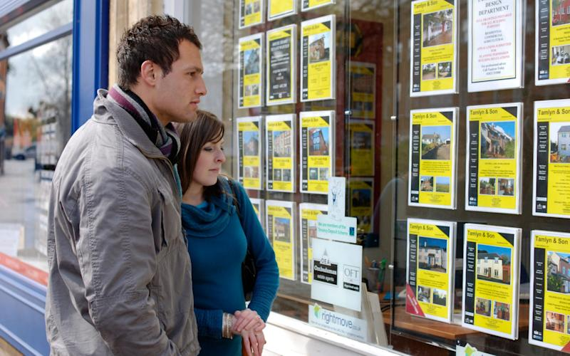 A young couple browse the listings in an estate agency window - Alamy Pay