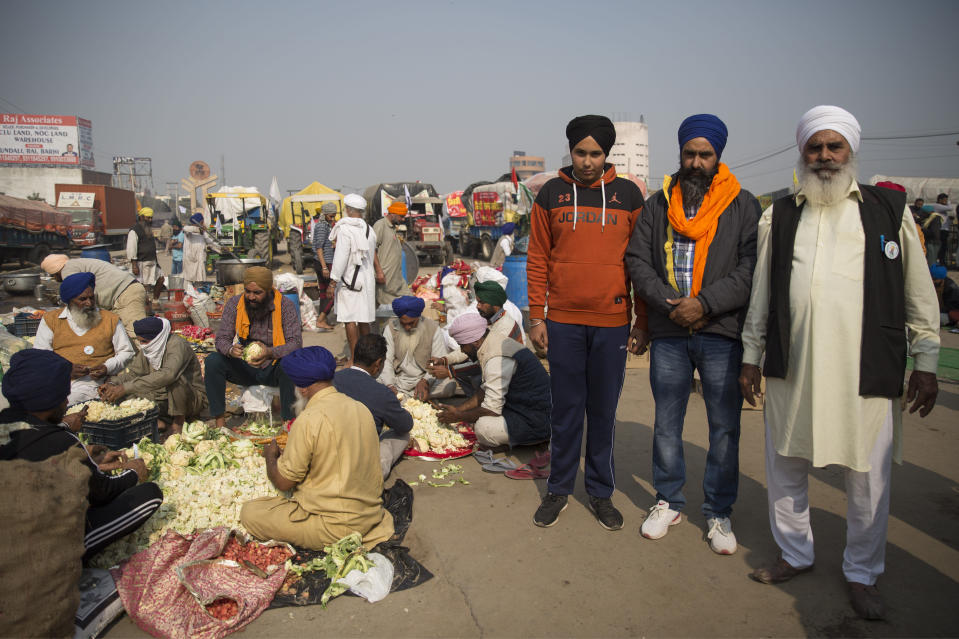 "Kulwant Singh, 72, right, stands for a photograph with his son, Baljeet Singh, 41, center, and grandson Amrinder Singh, 16, as they participate in farmers protest against new farming laws, at the Delhi-Haryana state border, India, Tuesday, Dec. 1, 2020. Singh said that when he left his home in Haryana for the protests which he called ""Qilah Fatehi,"" an Urdu term that translates to ""laying a siege,"" he gave his wife a garland of flowers for two possible scenarios. ""Either I return victorious and she places it around my neck in celebration, or I die here revolting and the same garland is put on my body when it reaches home,"" Singh said. His grandson Amrinder said ""It's a fight for my generation too."" (AP Photo/Altaf Qadri)"