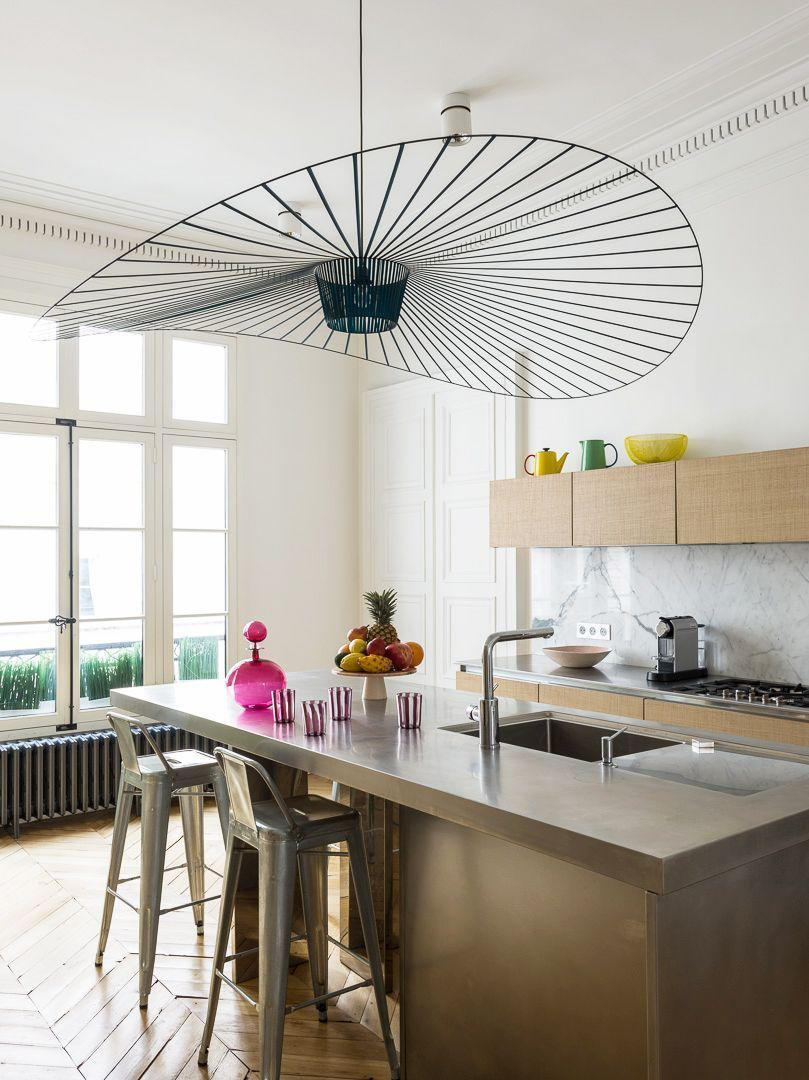 "<p>Now <em>this</em> is how you light up a room. In this Parisian apartment by <a href=""http://studiorazavi.com/"" rel=""nofollow noopener"" target=""_blank"" data-ylk=""slk:Studio Razavi"" class=""link rapid-noclick-resp"">Studio Razavi</a>, the dramatically large, undulating pendant opens everything up in one sweep. A fun magenta carafe adds a pop of color to the industrial kitchen.</p>"