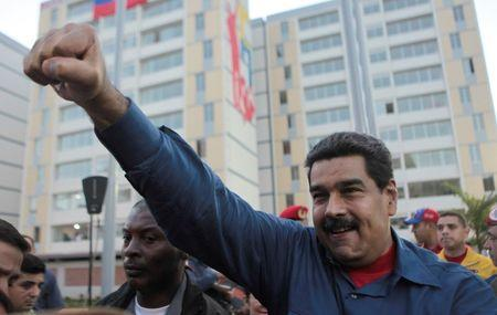 Venezuela's President Nicolas Maduro greets supporters as he arrives to an event for handing over houses in Caracas