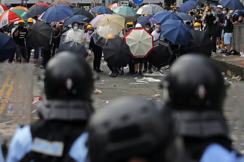 In this photo taken on Wednesday, June 12, 2019, protestors wear masks and helmets and hold umbrellas to protect their identities and provide cover from tear gas and pepper spray, as they clash with police near the Legislative Council in Hong Kong. Young Hong Kong residents protesting a proposed extradition law that would allow suspects to be sent to China for trial are seeking to safeguard their identities from potential retaliation by authorities employing mass data collection and sophisticated facial recognition technology. (AP Photo/Kin Cheung)
