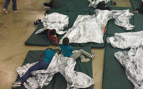 Children who've been taken into custody related to cases of illegal entry into the United States, rest in one of the cages at a facility in McAllen, Texas - Credit: AP