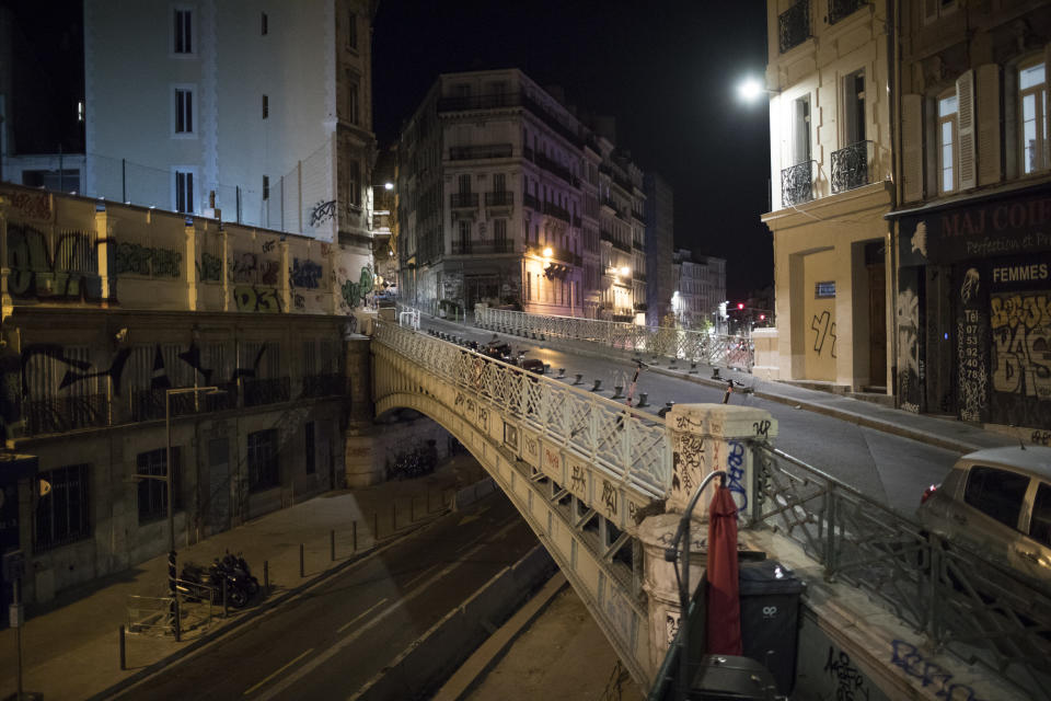 Empty streets are pictured after curfew in Marseille, southern France, Sat, Oct. 24, 2020. The curfew imposed in eight regions of France last week, including Paris and its suburbs, is being extended to 38 more regions and Polynesia. (AP Photo/Daniel Cole)