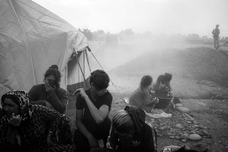 A newly arrived refugee family huddles together as dust from ongoing construction lingers in the air at the Gawilan camp in early November. | Moises Saman—Magnum Photos for TIME