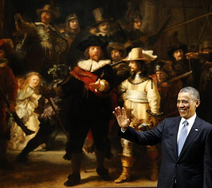 In this March 24, 2014, photo, U.S. President Barack Obama waves in front of Dutch master Rembrandt's The Night Watch painting during a visit to the Rijksmuseum in Amsterdam, Netherlands. From the heart of Europe to the expanse of Saudi Arabia's desert, Obama's weeklong overseas trip amounted to a reassurance tour for stalwart, but sometimes skeptical, American allies. At a time when Obama is grappling with crises and conflict in both Europe and the Middle East, the four-country swing also served as a reminder that even those longtime partners still need some personal attention from the president. (AP Photo/Frank Augstein)