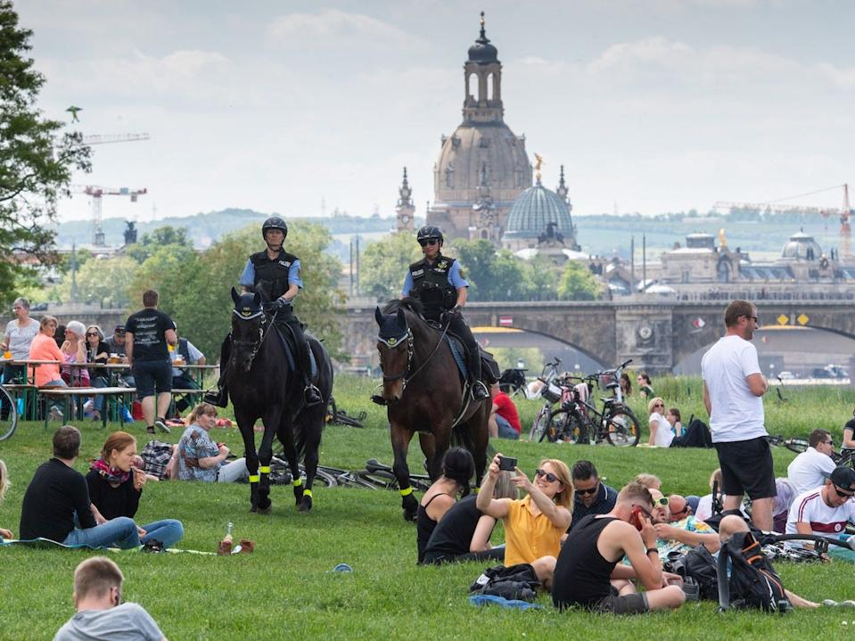 Policewomen of the Saxon police riding team patrol on their horses at a beer garden on the banks of the Elbe in Dresden, Germany on May 21, 2020.