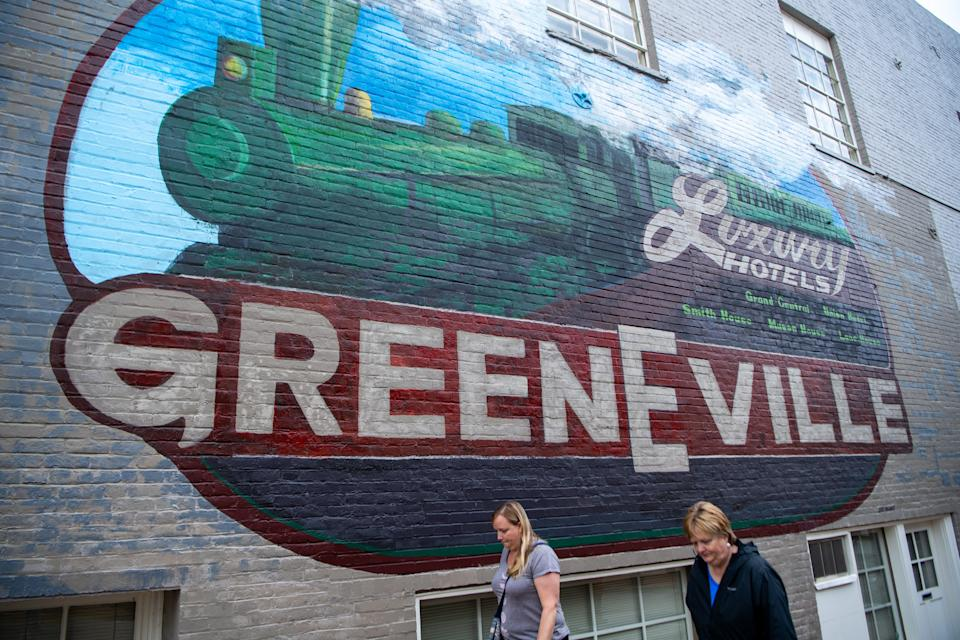 People walk past a downtown mural Friday, April 12, 2019, in Greeneville, Tenn.