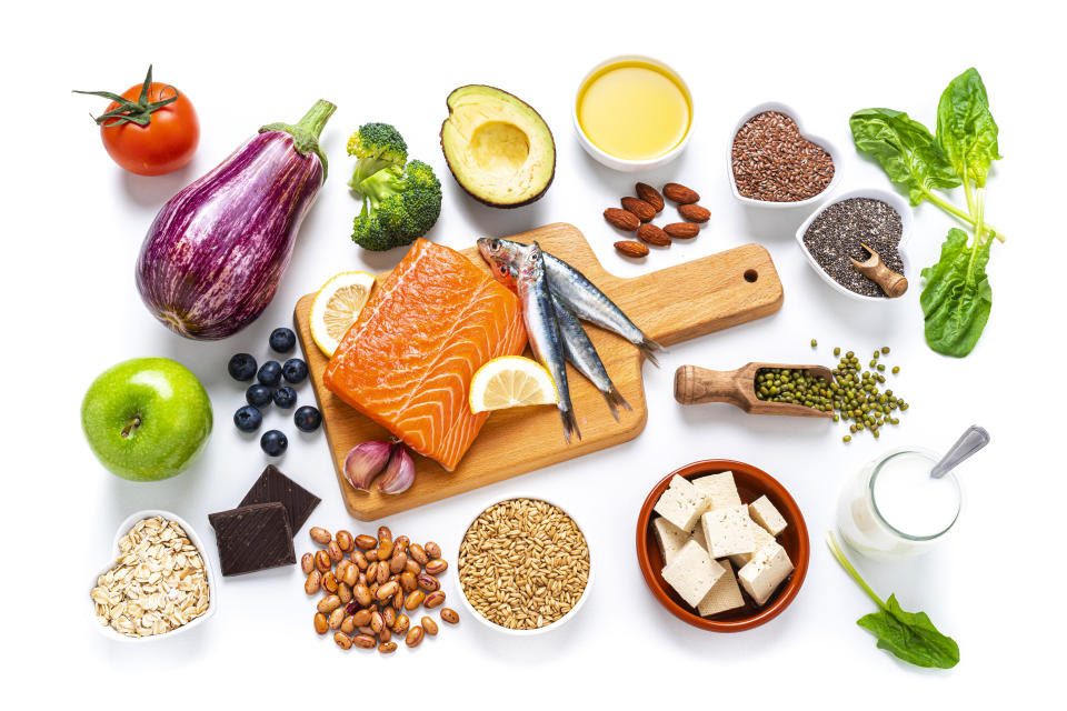 Healthy eating: group of fresh multicolored foods to help lower cholesterol levels shot from above on white background. The composition includes oily fish like salmon and sardines. Beans like Pinto beans and brown lentils. Vegetables like garlic, avocado, broccoli, eggplant and tomatoes. Fruits like apple, grape, orange and berries. Nuts like almonds and walnuts. Soy products like tofu and soy milk. Cereals and seeds like chia seeds, flax seeds, oatmeal and barley. Olive oil and yogurt with added sterols and stanols. High resolution 42Mp studio digital capture taken with SONY A7rII and Zeiss Batis 40mm F2.0 CF lens