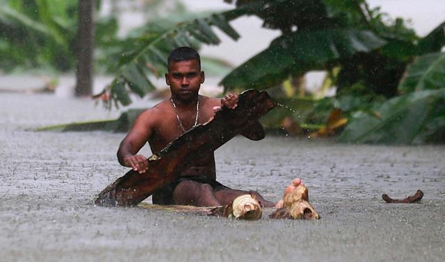 <p>A Sri Lankan man rows a makeshift raft on a flooded road in Wehangalla village in Kalutara district, Sri Lanka, Saturday, May 27, 2017. (AP Photo/Eranga Jayawardena) </p>