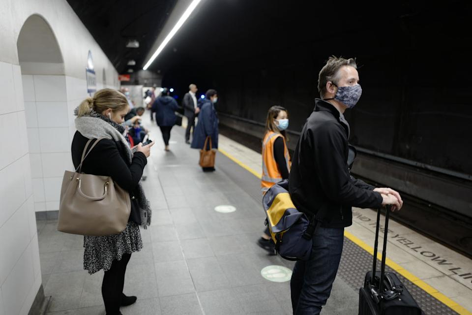 Rush-hour commuters wear face masks at Wynyard Station in Sydney, Australia.
