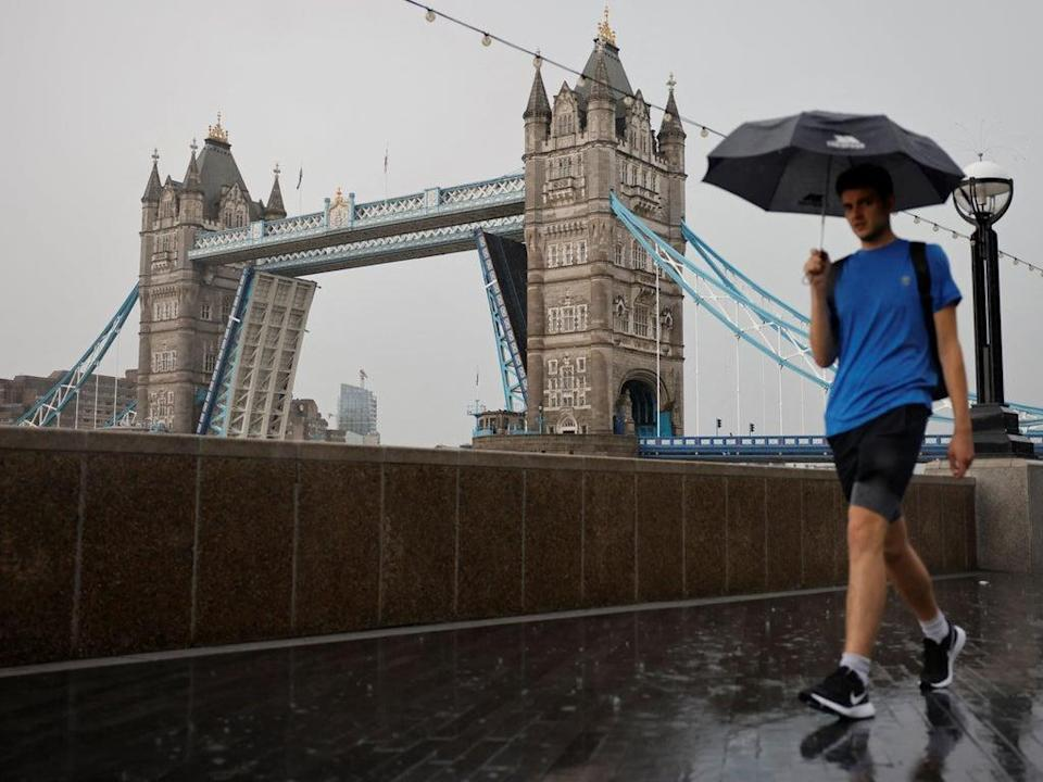 A man is pictured walking in the rain by London's Tower Bridge earlier this month  (AFP via Getty Images)