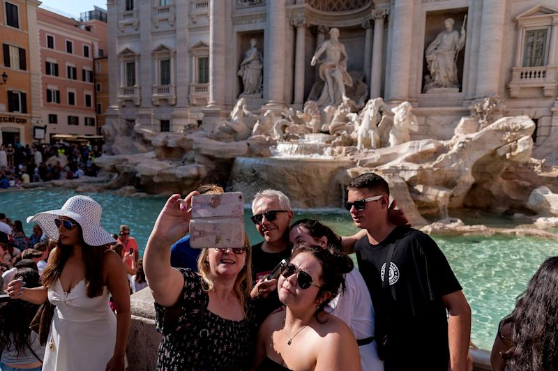 ROME, ITALY - AUGUST 29: Tourists take a selfie picture with a mobile phone in front of the Trevi Fountain on August 29, 2018 in Rome, Italy. Every day thousands of tourists visit the Trevi Fountain, which has become a real institution for tourists, who try their hand at the famous toss of a coin and take selfie and souvenir photos using this beautiful historical building as a backdrop.(Photo by Stefano Montesi - Corbis/Getty Images)
