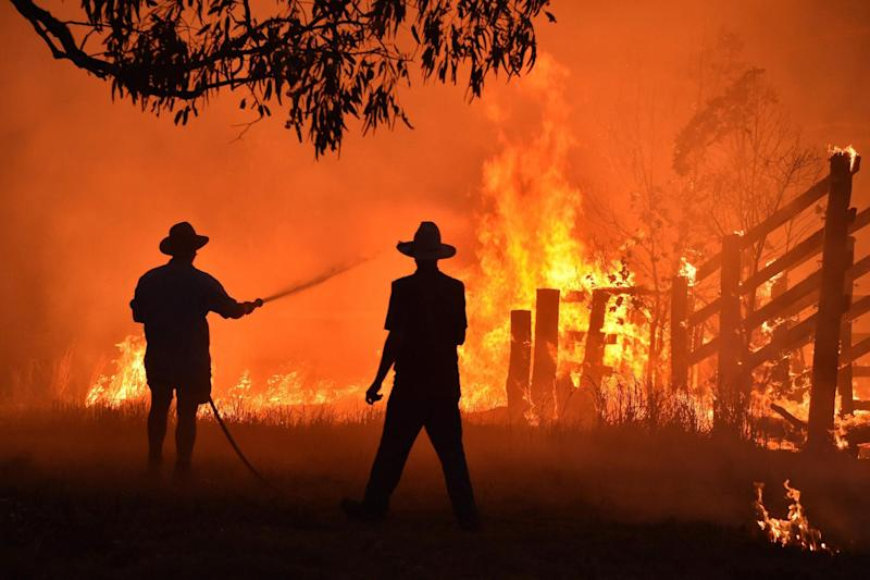 Residents defend a property from a bushfire at Hillsville near Taree, 350km north of Sydney: AFP via Getty Images
