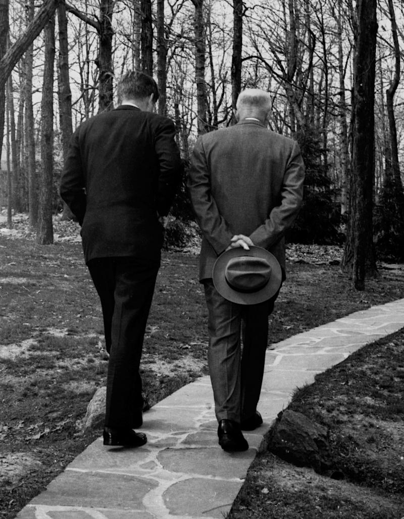 With their heads bowed, President John F. Kennedy, left, walks along a path at Camp David near Thurmond, Md., with former President Dwight D. Eisenhower, April 22, 1961, as the two met to discuss the Bay of Pigs invasion. (AP Photo/Paul Vathis) ORG XMIT: APHS112