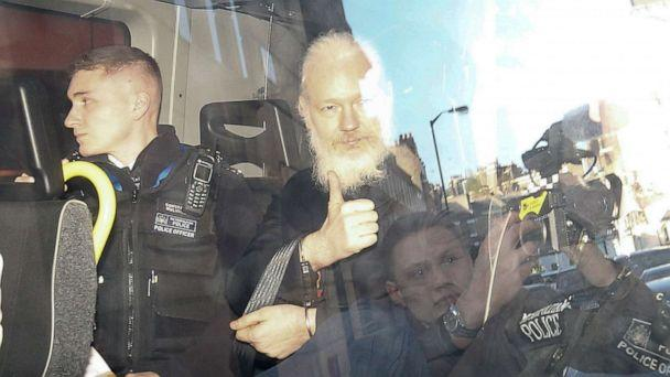 PHOTO: WikiLeaks founder Julian Assange gestures as he leaves the Westminster Magistrates Court in the police van, after he was arrested in London, April 11, 2019. (Henry Nicholls/Reuters)