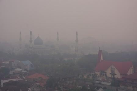 A mosque and a church are pictured as smog covers the city due to the forest fire in Pekanbaru