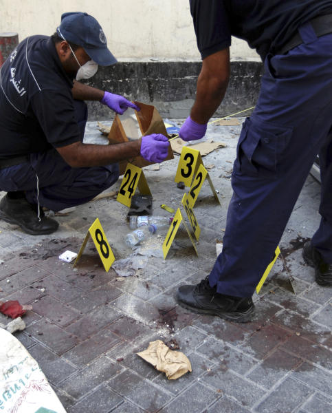 Bahraini policemen collect evidence at the scene of an explosion that killed an Asian man in Manama, Bahrain, on Monday, Nov. 5, 2012. A series of bomb blasts in Bahrain's capital killed at least two people Monday, authorities said, a sign that some factions within the opposition may be increasingly turning to violence in the nearly 21-month uprising against the Gulf nation's Western-backed rulers. (AP Photo/Hasan Jamali)