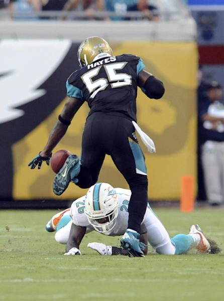 Jacksonville Jaguars outside linebacker Geno Hayes (55) defends as Miami Dolphins running back Lamar Miller (26) can't hang on to a pass during the first half of an NFL preseason football game, Friday, Aug. 9, 2013, in Jacksonville, Fla. (AP Photo/Stephen Morton)