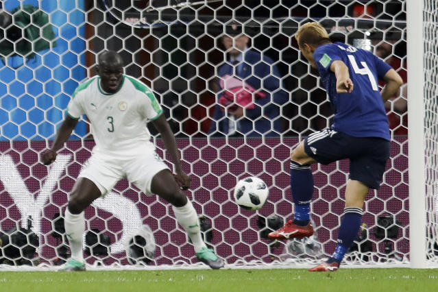 Japan's Keisuke Honda, right, scores his side's second goal past Senegal's Kalidou Koulibaly during the group H match between Japan and Senegal at the 2018 soccer World Cup at the Yekaterinburg Arena in Yekaterinburg , Russia, Sunday, June 24, 2018. (AP Photo/Natacha Pisarenko)