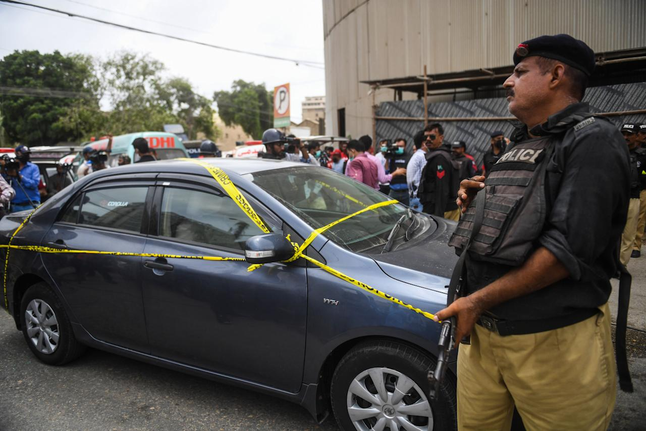 A policeman guards a car used by alleged gunmen outside the Pakistan Stock Exchange building in Karachi on June 29, 2020. - Gunmen attacked the Pakistan Stock Exchange in Karachi on June 29, with four of the assailants killed, police said. (Photo by Asif HASSAN / AFP) (Photo by ASIF HASSAN/AFP via Getty Images)