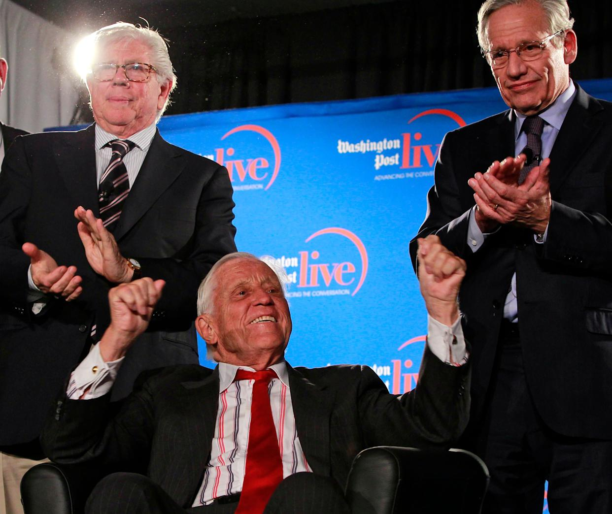 Former Washington Post reporters Carl Bernstein, left, and Bob Woodward, right, applaud as former executive editor Ben Bradlee sits on stage during an event sponsored by The Washington Post to commemorate the 40th anniversary of Watergate Monday, June 11, 2012 at the Watergate office building in Washington. (AP Photo/Alex Brandon)