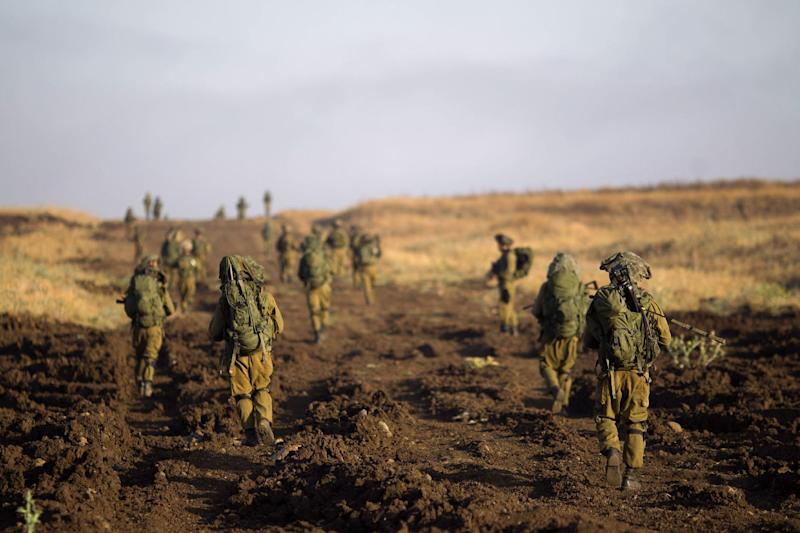 Israeli soldiers of the Golani brigade march during training in the Israeli controlled Golan Heights near the border with Syria Wednesday, June 26, 2013. (AP Photo/Ariel Schalit)