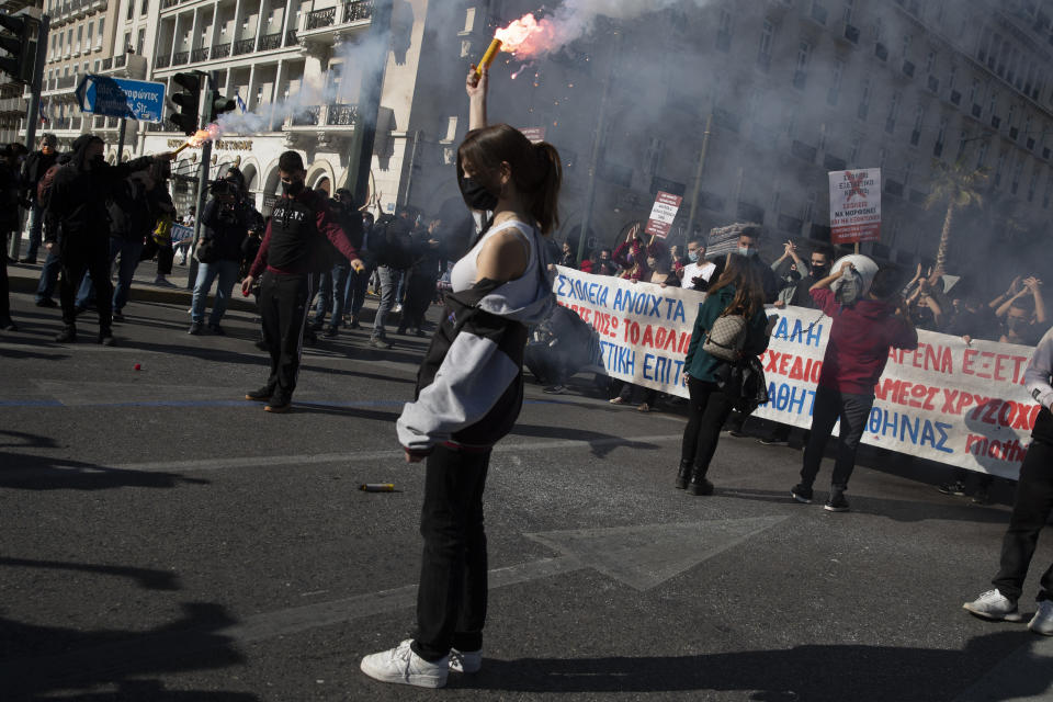 University students wearing face masks to protect against coronavirus, hold up flares during protest against education reforms in Athens, Thursday, Feb. 4, 2021. Thousands of protesters in Greece have held demonstrations in the Greek capital and the second largest city of Thessaloniki against plans by the government to police university campuses (AP Photo/Petros Giannakouris)