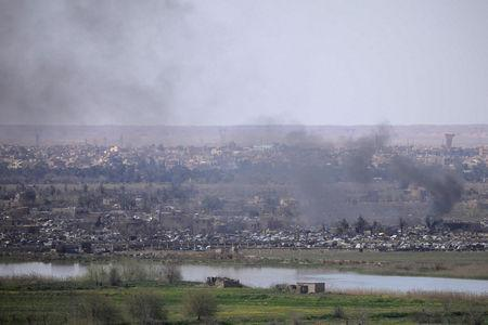 FILE PHOTO: Smoke rises from the last besieged neighborhood in the village of Baghouz, Deir Al Zor province, Syria, March 20, 2019. Picture taken March 20, 2019. REUTERS/Rodi Said/File Photo