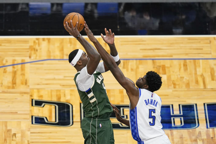 Milwaukee Bucks center Bobby Portis, left, attempts a shot over Orlando Magic center Mo Bamba (5) during the second half of an NBA basketball game, Sunday, April 11, 2021, in Orlando, Fla. (AP Photo/John Raoux)