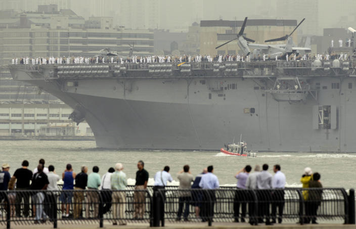 People watch the USS Wasp sail up the Hudson River from Jersey City, N.J., Wednesday, May 23, 2012. Naval vessels ranging from a U.S. amphibious assault ship to a Finnish minelayer are participating in New York City's Fleet Week. (AP Photo/Seth Wenig)