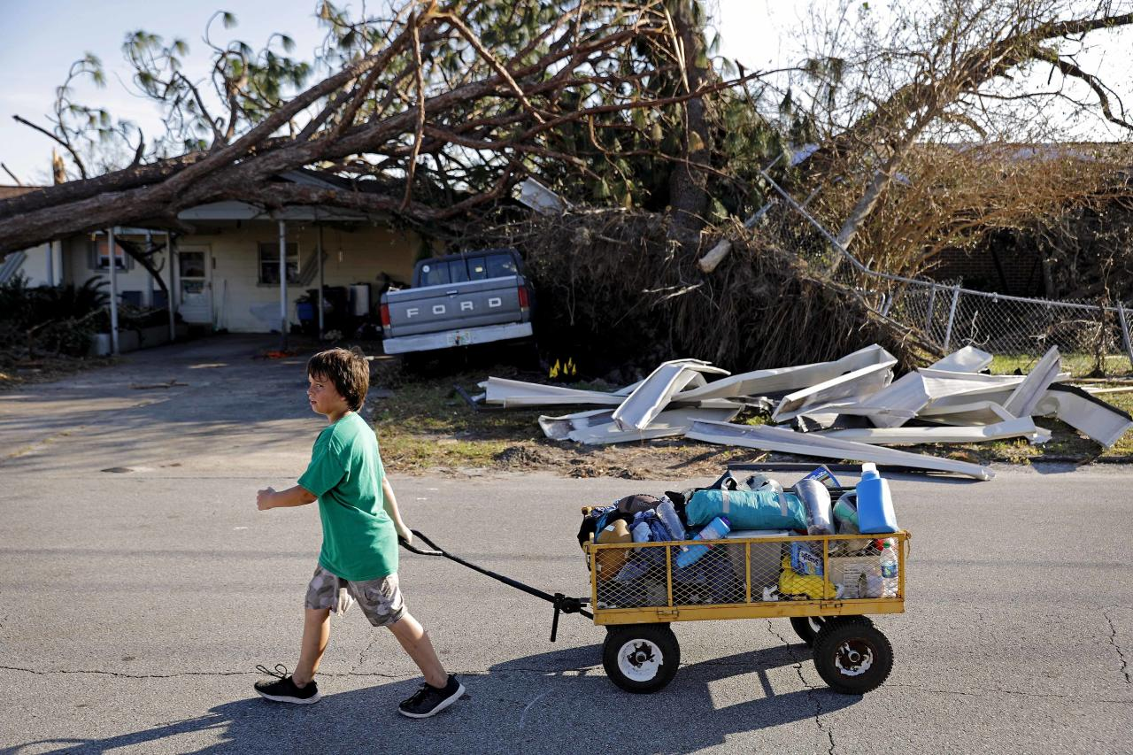Anthony Weldon, 11, pulls a cart with his family's belongings as they relocate from their uninhabitable damaged home to stay at their landlord's place in the aftermath of Hurricane Michael in Springfield, Fla., Monday, Oct. 15, 2018. (AP Photo/David Goldman)