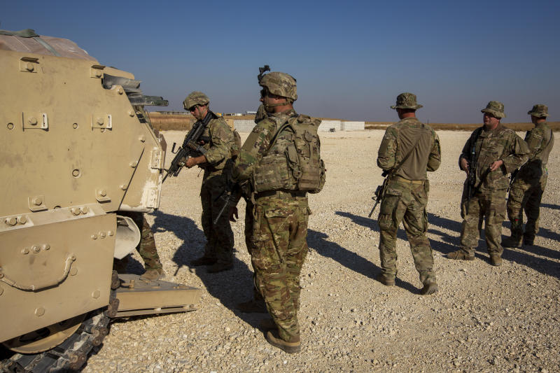 A group of U.S. soldiers board fighting vehicles at a US military base at undisclosed location in Northeastern Syria, Monday, Nov. 11, 2019. A senior U.S. coalition commander said Friday, Nov. 15,  the partnership with Syrian Kurdish forces remains strong and focused on fighting the Islamic State group, despite an expanding Turkish incursion on areas of Kurdish control. (AP Photo/Darko Bandic)