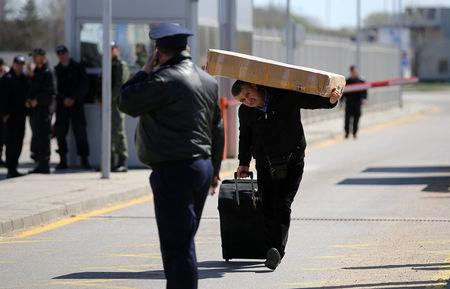 Man carries his luggage as he crosses the border crossing between Turkey and Bulgaria on foot during a protest at Kapitan Andreevo border checkpoint