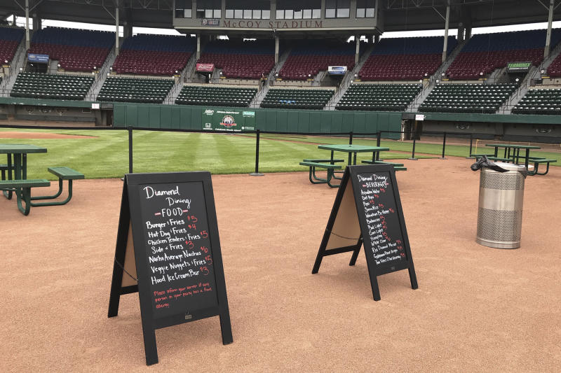 """Menu boards and tables occupy the third base infield dirt in preparation for dining guests at McCoy Stadium, home of the Pawtucket Red Sox, in Pawtucket, Rhode Island, Wednesday, May 27, 2020. With the minor league baseball season on hold due to the coronavirus pandemic, the Triple-A affiliate of the Boston Red Sox had found another use for its home field. Starting next weekend, """"Dining on the Diamond"""" will allow PawSox fans and others just longing for a taste of baseball to sample typical ballpark fare on the McCoy Stadium infield.(AP Photo/Jimmy Golen)"""