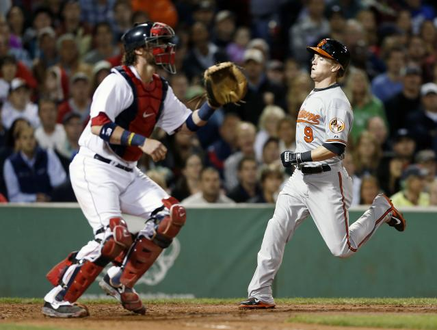 Baltimore Orioles' Nate McLouth (9) scores on a two-run double by Manny Machado as Boston Red Sox's Jarrod Saltalamacchia waits for the throw in the third inning of a baseball in Boston, Thursday, Aug. 29, 2013. (AP Photo/Michael Dwyer)