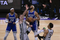 Sacramento Kings forward Marvin Bagley III (35) is fouled on his way to the basket by San Antonio Spurs forward Keldon Johnson (3) as Spurs center Jakob Poeltl (25) helps defend during the first quarter of an NBA basketball game in Sacramento, Calif., Friday, May 7, 2021. (AP Photo/Hector Amezcua)