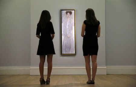 """Two Sotheby's employees pose with """"Bildnis Gertrude Loew (Gertha Felsovanyi)"""" by Gustav Klimt at Sotheby's in London"""