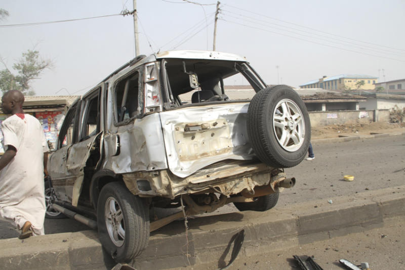 A man walk past a damaged car at the site of a bomb explosion at a road in Kaduna, Nigeria on Sunday, April 8, 2012. An explosion struck Kaduna, that has seen hundreds killed in religious and ethnic violence in recent years, causing unknown injuries as diplomats had warned of possible terrorist attacks over the Easter holiday, police said.(AP Photos/Emma Kayode)