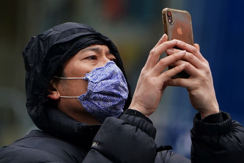 A man takes a photo in Times Square ahead of New Year's Eve