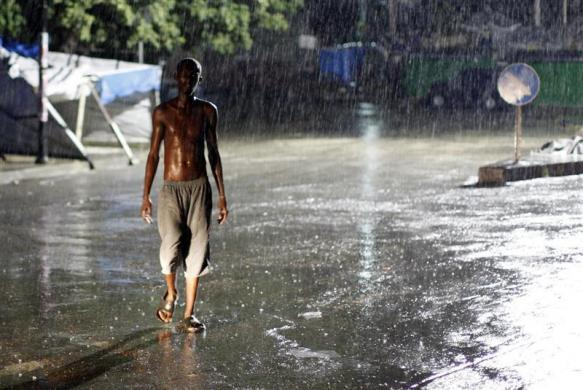 A man walks in the rain at down town Port-au-Prince, October 31, 2010.
