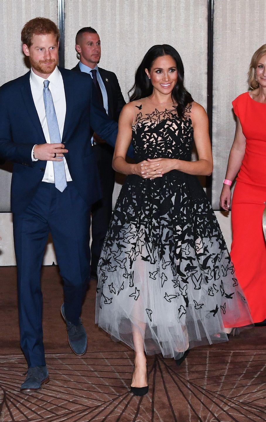 """<p>Back in Sydney after a whirlwind day in Tonga, Harry and Meghan changed into formal attire for an elegant evening at the Australian Geographic Society Awards. The Duchess <a href=""""https://www.townandcountrymag.com/style/fashion-trends/a24230198/meghan-markle-oscar-de-la-renta-gown-sydney-australia-royal-tour/"""" rel=""""nofollow noopener"""" target=""""_blank"""" data-ylk=""""slk:wore a black and white gown"""" class=""""link rapid-noclick-resp"""">wore a black and white gown</a> by Oscar de la Renta for the night. </p>"""