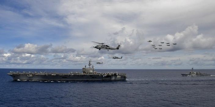 Aircraft from Carrier Air Wing 5 and Carrier Air Wing 17 fly in formation over the Nimitz Carrier Strike Force (CSF). The USS Nimitz (CVN 68) and USS Ronald Reagan (CVN 76) Carrier Strike Groups are conducting dual carrier operations in the Indo-Pacific as the Nimitz CSF