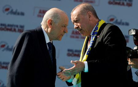 FILE PHOTO: Turkish President Tayyip Erdogan and Devlet Bahceli, leader of Nationalist Movement Party (MHP), talk on the stage during a rally ahead of local elections, in Ankara, Turkey, March 23, 2019. REUTERS/Umit Bektas/File Photo